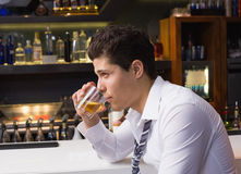 Young man drinking whiskey neat Royalty Free Stock Image