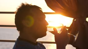 Young man is drinking white wine from a glass in a cafe at sunset near the sea. A young man is drinking white wine from a glass in a cafe at sunset near the sea Royalty Free Stock Image