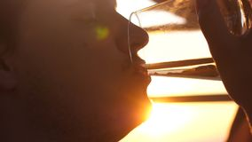 Close up of man is drinking white wine from a glass in a cafe at sunset near the sea. A young man is drinking white wine from a glass in a cafe at sunset near Royalty Free Stock Photo
