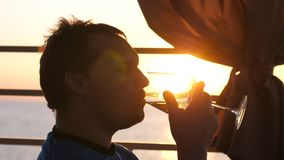 Young man is drinking white wine from a glass in a cafe at sunset near the sea. A young man is drinking white wine from a glass in a cafe at sunset near the sea Stock Photo