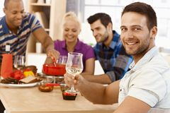 Young man drinking wine with friends royalty free stock image