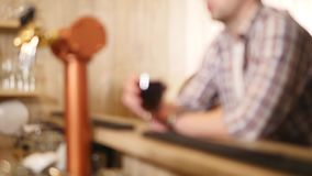 Young man drinks beer behind a bar counter. Selective Focus.  stock video