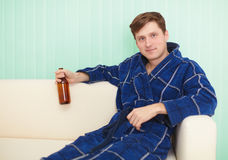 Young man drinks beer in dressing gown on sofa Stock Photo