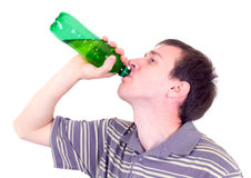 The young man drinks from a bottle. The young man drinks from a green bottle Royalty Free Stock Photos