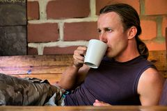 Young man drinks coffee lying next to fire Royalty Free Stock Photo