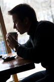 Young man drinks coffee in a restaurant Royalty Free Stock Image