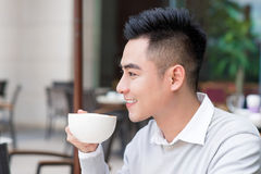 Young man drinks coffee on the street. Man drinks coffee. Young man drinks coffee outdoor. Businessman drinks coffee outdoor. Man. Drink coffee in cafe. Cozy Royalty Free Stock Images