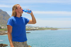 Young man drinks from water bottle Royalty Free Stock Photo