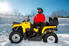 Free Young Man Driver In Red Warm Winter Clothes And Black Helmet On The ATV 4wd Quad Bike Stand In Heavy Snow With Deep Royalty Free Stock Photo - 140134785