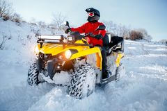 Free Young Man Driver In Red Warm Winter Clothes And Black Helmet On The ATV 4wd Quad Bike Stand In Heavy Snow With Deep Royalty Free Stock Image - 140135906
