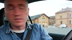 A young man driver moves in reverse. Close-up portrait in the car.  stock video footage
