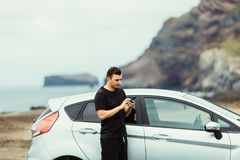 Young man driver near car use phone on summer vocation with ocean rock on background. Car rental trip. royalty free stock photos