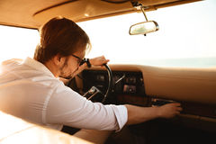 Young man driver turning on stereo system. While sitting in a retro car with hand on a steering wheel royalty free stock images