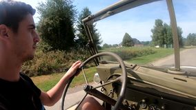 Young man driving an antique military car on dirt road. A young man driving an antique military car on dirt road stock video