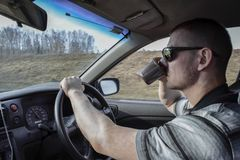 A young man driving a car drinking coffee. Dangerous situation on the road. stock photo