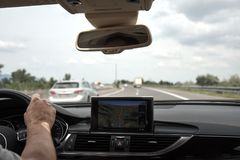 A young man driving a car on a highway, holding a steering wheel. A young man driving a car on a highway with moving cars, holding a steering wheel, navigation Stock Photo