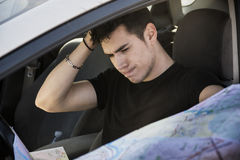 Young Man Driving the Car, Holding a Map Confused Royalty Free Stock Photo