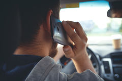 Young man driving a car with phone. Young man driving a car, talking on mobile phone. Multitasking. Don't talk and drive Royalty Free Stock Photography