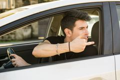 Young Man Driving a Car and showing the middle Royalty Free Stock Photography