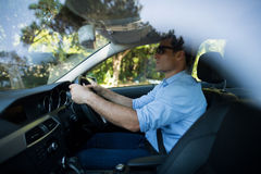 Young man driving car. Side view of young man driving car Royalty Free Stock Images