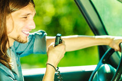 Young man driving car using cb radio Stock Images