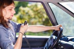 Young man driving car using cb radio Stock Photo