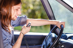 Young man driving car using cb radio Royalty Free Stock Photo