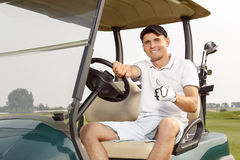 Young man driving cart on a golf course Stock Image