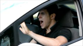 Young man driving drinking alcohol and honking stock footage
