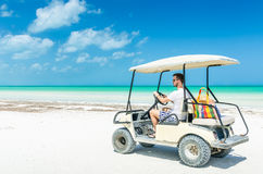 Young man driving golf cart along tropical white sandy beach Royalty Free Stock Images