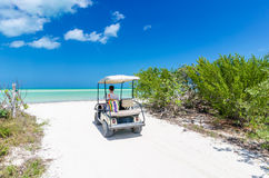 Young man driving on a golf cart at tropical white sandy beach Stock Photos