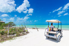 Young man driving on a golf cart at tropical white sandy beach Stock Images