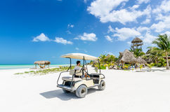 Young man driving on a golf cart at tropical white sandy beach royalty free stock image