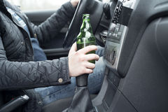 Young man driving his car while drinking alcohol Royalty Free Stock Image
