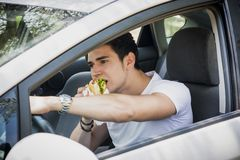 Young man driving his car while eating food Stock Images