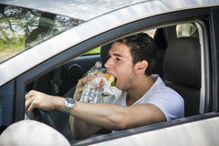 Young man driving his car while eating food royalty free stock image