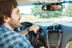 Young man driving his car. Young handsome guy driving his new car Stock Images