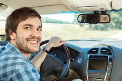 Young man driving his car. Young man smiling to camera in the car Royalty Free Stock Photos
