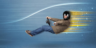 Young man driving in imaginary fast car with blurred lines Royalty Free Stock Images