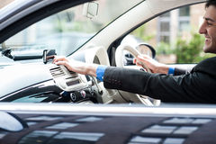 Young man driving a nice car, using gps device Royalty Free Stock Image