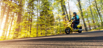 Young man driving scooter, blur motion Stock Image
