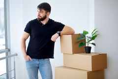 Young man dropping cardboard box. Moving into new home.  Stock Image
