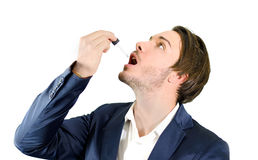 Young man dropping medicine or drug treatment with dropper. Young man using dropper pipette on his mouth for medicine, drug treatment Royalty Free Stock Image