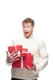 Young man drops many red christmas gifts. Young casual caucasian man drops many red christmas gifts with funny expression Royalty Free Stock Photos