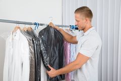 Young man in dry cleaning store. Young Man Getting Coat In Dry Cleaning Store Stock Photos