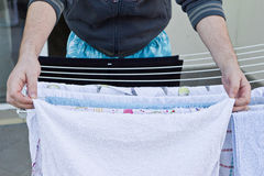 Young man drying clothes after laundry Royalty Free Stock Photo