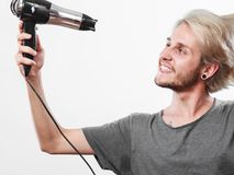 Young man drying hair with hairdryer Royalty Free Stock Image