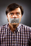 Young man with duct tape over his mouth Stock Image
