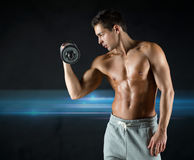 Young man with dumbbell flexing biceps Royalty Free Stock Photos