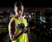 Young man with dumbbell flexing biceps. Sport, bodybuilding, training and people concept - young man with dumbbell flexing biceps over night city background Stock Photography